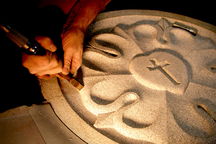 A man's hands using a chisel to carve a granite memorial VTP Vermont Training Program