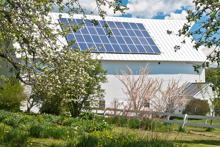 White barn with solar panels on its roof earth day