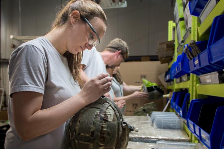Woman working on a military helmet Revision Ballistics VTP