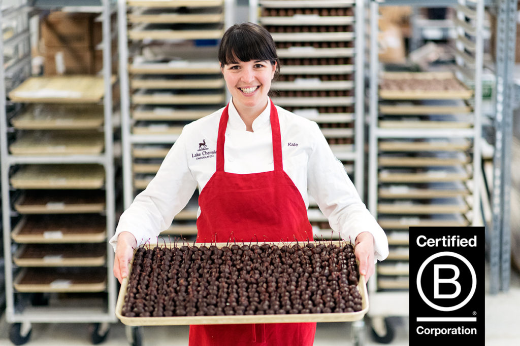 young woman holding tray of chocolate candies B Corp logo triple bottom line socially responsible employee owned